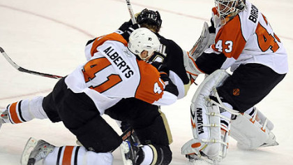Jordan Staal is sandwiched between Flyers Andrew Alberts and goaltender Martin Biron in overtime.
