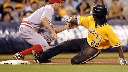 Pirates' Andrew McCutchen slides safely into third with a triple against Reds Adam Rosales in the fifth inning tonight at PNC Park.