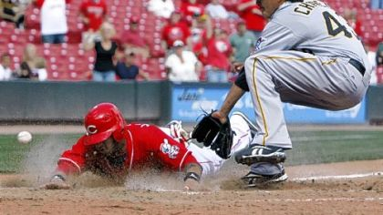 Reds outfield Darnell McDonald slides across home plate with the winning run after a wild pitch from Pirates pitcher Jesse Chavez, covering home at right, in the bottom of ninth inning of Game 1 of a doubleheader yesterday.