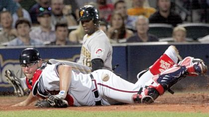 Atlanta catcher Brian McCann can't handle the throw from second base, allowing Craig Monroe to score on Adam LaRoche's single in the seventh inning.