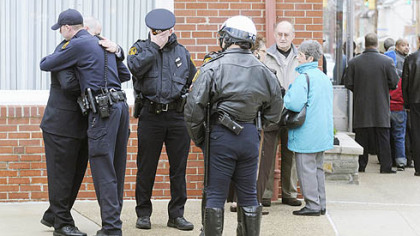 Police embrace outside the Winter Funeral Home in Bloomfield during visitation for fellow officer Paul J. Sciullo II.