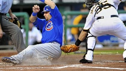 The Cubs' Jake Fox slides safely into home in the second inning as Jason Jaramillo cannot apply the tag in time because center fielder Andrew McCutchen's throw was high.
