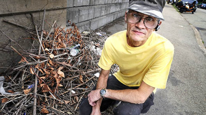 Paul McCarthy, 62, of Greenfield, next to some trash that remained after he cleaned up the hillside and sidewalk.