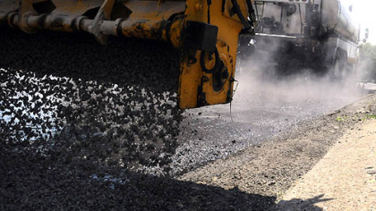 "The ""chipper"" applies a layer of gravel over a hot steaming coating of the E-3 modified  oil on the surface  of East Willock Road in Whitehall last week."