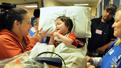 Transplant patient Oliver Wilhelm III, 5, of Kingwood, W.Va., gives a thumbs-up to his mom, Crystal at the old Children's Hospital in Oakland before he was being transferred to the new hospital this morning. He is among 178 patients being transported to the new Lawrenceville location.  At right is registered nurse Christin Cooper and Oliver's father, Oliver Wilhelm, Jr.