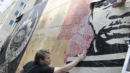 Shepard Fairey puts up a poster on a wall across the street from the Warhol Museum on the North Shore.