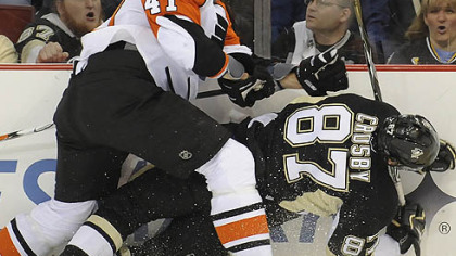 The Flyers' Andrew Alberts checks Sidney Crosby into the boards in the second period last night.