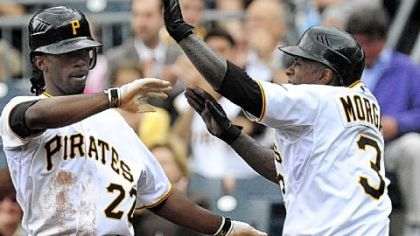 Andrew McCutchen, left, and Nyjer Morgan, right, high-five at the plate after scoring during the second inning of a baseball game against the Mets, Thursday.
