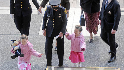 The family of slain Officer Stephen J. Mayhle ? widow Shandra, rear second from left, and daughters Jennifer, 6, and Brooklynn, 3 ? arrives for the final viewing at the City-County Building yesterday.