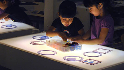 Four-year-old twins Uma and Jayanthi Simhan work on a light table with different shapes at Shady Lane School in Point Breeze.