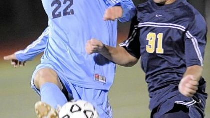 Mt. Lebanon's Evan Schardt, left, beating Kiski Area's Mike Geiselhart to the ball during a WPIAL playoff match last season, leads the defense for top-ranked Blue Devils.