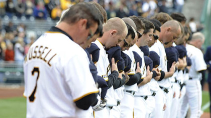 Led by manager John Russell, Pirates players observe a moment of silence in memory of three fallen police officers during Opening Day ceremonies yesterday at PNC Park.