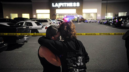 Theresa Smith, left, 18, and friend Ashley Slifko, 19, embrace outside LA Fitness last night in Collier. Ms. Smith?s sister, Tracey, was inside during the shooting but escaped unharmed.