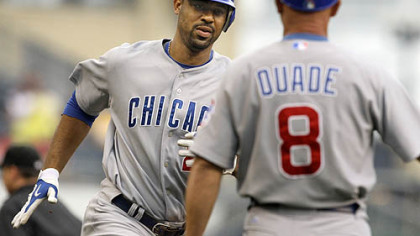 Cubs first baseman Derrek Lee rounds third to greetings from coach Mike Quade after hitting a solo homerun off Pirates pitcher Daniel McCutchen during the first inning.