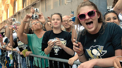 Fans cheer the Penguins as they parade along Grant Street.