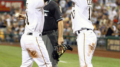 Pirates pinch hitter Steve Pearce, left, is greeted at home plate by teammate Ronny Cedeno after driving Cedeno in during the sixth inning. Pearce''s hit drove in Cedeno and Pearce scored on an error.
