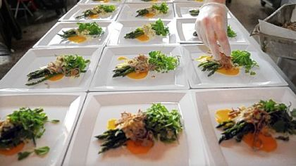 "The finishing touches are put on the asparagus salad at the ""underground"" dinner by chef Kevin Sousa."