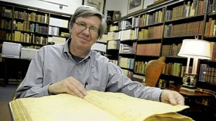 Amateur historian Michael Shealey with the Old Stone Tavern ledger from 1793 to 1796 in the William R. Oliver Special Collections room in the Carnegie Library, of Pittsburgh Oakland.