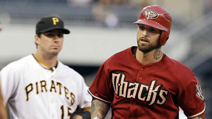 Diamondbacks infielder Ryan Roberts rounds third past Pirates third baseman Andy LaRoche after hitting a two-run home run off Pirates pitcher Zach Duke.