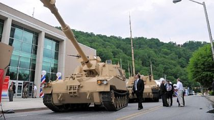 Visitors look over the display of vehicles by BAE Systems at the Showcase for Commerce at the Cambria County War Arena in Johnstown.  Among them is this Paladin Integrated Management vehicle.