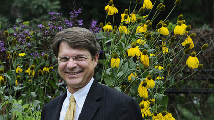 Richard Piacentini, executive director of Phipps Conservatory, brings his work home in his rain garden. Behind him are ironweed, left, and Helianthus.