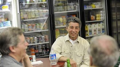 Co-owner John Prodan chats with customers inside the Frick Park Market in Point Breeze on a recent Friday.