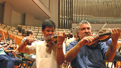 Violinst Christopher Wu (left) and concertmaster Andres Cardenes warming up with other members of the Pittsburgh Symphony at the
