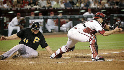 Pirates outfielder Brandon Moss scores on an RBI double by third baseman Andy LaRoche as Diamondbacks catcher Miguel Montero waits for the throw during the fourth inning.