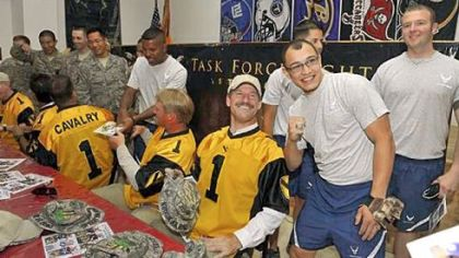 Bill Cowher, the former head coach of the Pittsburgh Steelers, poses with U.S. Air Force SRA Jonathan Echevarria at Forward Operating Base Warrior near Kirkuk, Iraq, Thursday.