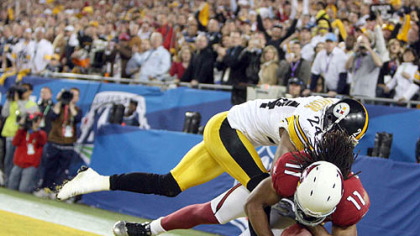 Cardinals receiver Larry Fitzgerald pulls in a touchdown catch against Ike Taylor midway through the fourth quarter last night.