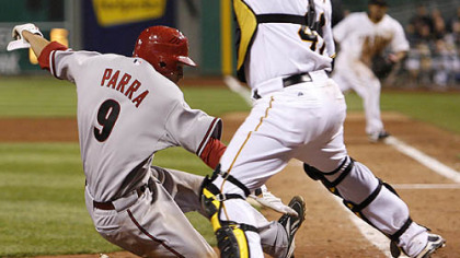 Pirates catcher Ryan Doumit reaches for the throw as Diamondbacks outfielder Garardo Parra scores one of the Diamondbacks five runs in the 12th inning.