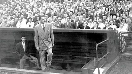 The Rev. Billy Graham emerges from the Pirates' dugout at Forbes Field to deliver a sermon in his first visit in September 1952.