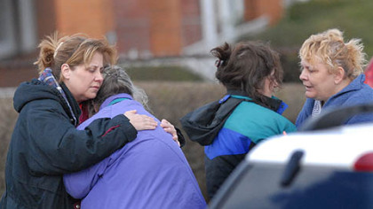 Family members of the suspect in this morning's deadly standoff offer each other comfort at the scene.