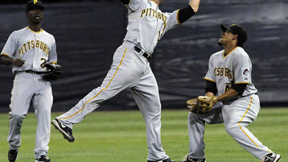 Pirates second baseman Freddy Sanchez, center, catches a shallow pop fly off the bat of Twins infielder Brendan Harris under the watch of center fielder Andrew McCutchen, left, and right fielder Delwyn Young, right, in the first inning last night's game.