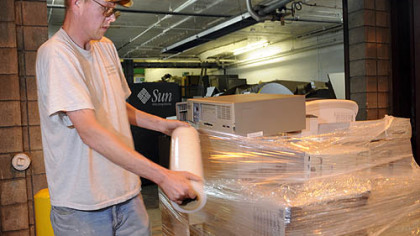 Paul Vareberg, foreman with  A. Greenspan Computer Recycling in Turtle Creek,  wraps computers for  shipment to Canada