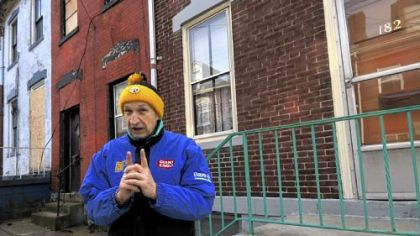 Pete Golovich in front of his home, on the right, and the connected row houses that are involved in a dispute with the water authority.
