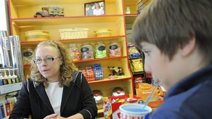 Maggi Cook, owner of the Frick Park Market in Point Breeze, takes orders for candy and slushies at the candy bar on a recent Friday.