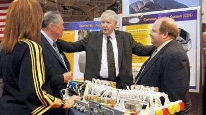 Rep. John P. Murtha, D-Johnstown, center, speaks on Friday with, from left, Karen Stiles, Jack Sweet and Joe Calin of Argon, an electronic defense contractor, at the Showcase for Commerce at the Cambria County War Arena in Johnstown.