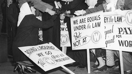 This image from 1946 shows Pittsburgh women seeking equal pay after World War II. In 1946, the United Electrical Workers struck for equal pay. The two men in this picture, Charles Copeland and Paul Carmichael of Local 601, toured the picket lines pretending to be Westinghouse executives. The company's executives, workers charged, made $149,000 a year but refused to give women equal pay for equal work.