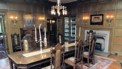 The dining room features oak paneling, an original chandelier and silver wall sconces. It overlooks the back lawn.