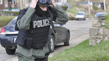 An officer dons his gear as police respond after a man involved in a domestic dispute opened fire on police today Stanton Heights, killing three officers and injuring two others.
