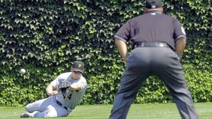Pirates right fielder Brandon Moss is unable to catch a line drive triple by Chicago Cubs' Sam Fuld as second base umpire Eric Cooper watches during the first inning of yesterday's game in Chicago.