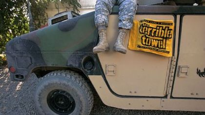 A member of the Pennsylvania National Guard sits on a Humvee draped with a Terrible Towel in January 2005 in Camp Habbaniyah, Iraq.