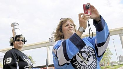Elaine Anderson, of Ross Township, takes a photo of the Penguins&#039; team bus arriving at Joe Louis Arena in Detroit yesterday.  At left is her friend, Christine Szymarek, of White Oak.