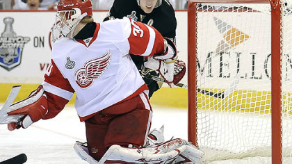 The Penguins' Evgeni Malkin slips the puck past Red Wings' goalie Chris Osgood in the first period at the Mellon Arena last night.