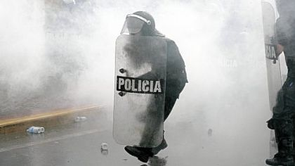 Surrounded by tear gas, police officers move forward during a protest against Venezuelan President Hugo Chavez in Caracas.