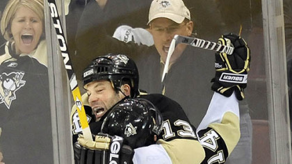 Bill Guerin gets a hearty hug from teammate Chris Kunitz after scoring the winning goal.