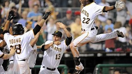Pirates' Andrew McCutchen leaps into his awaiting teammates after scoring the game-winning run against the Phillies at PNC Park tonight.
