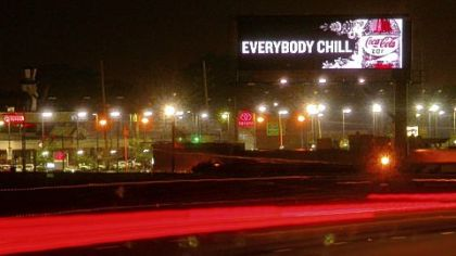 A Cola-Cola advertisement on a digital billboard dominates the night sky along a roadway in Cleveland.