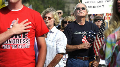 "From left, Medge Boyer, of Shaler; Paul Jones, of Finleyville, and Juanita Martini, of Elizabeth, recite the Pledge of Allegiance at a ""tea party"" rally at North Boundary Park in Cranberry yesterday afternoon."